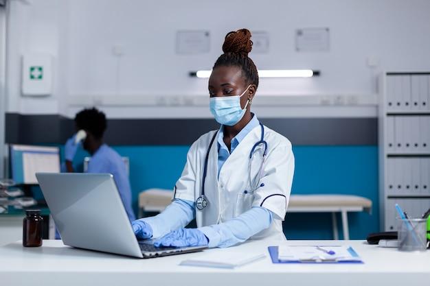 Афро-американский врач сидит за столом с ноутбуком