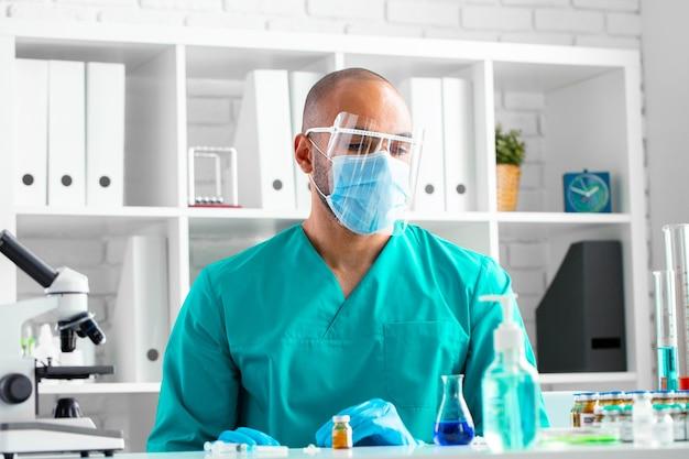 아프리카 계 미국인 의사는 테이블에 앉아 약물 주사를 준비