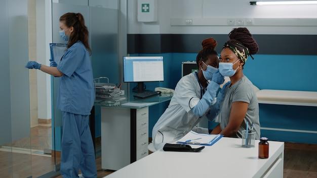Афро-американский врач с помощью отоскопа для осмотра уха
