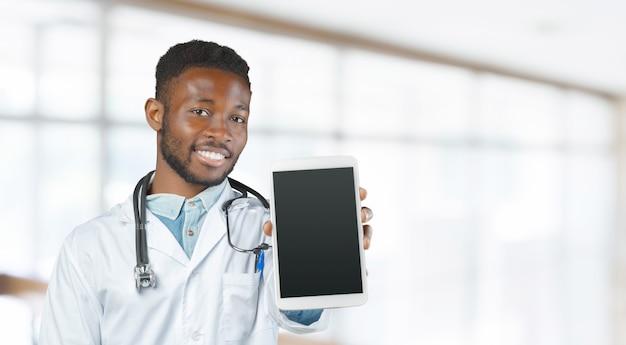 Афро-американский доктор с стетоскоп, стоя против размыты
