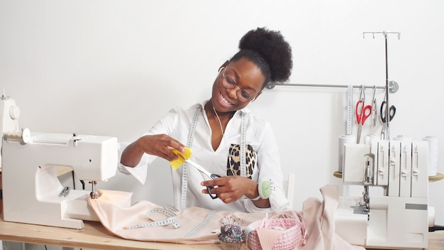 African-american dressmaker in light clothing sews clothes on a sewing machine
