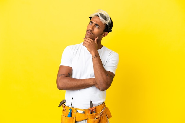 African american electrician man over isolated yellow wall and looking up