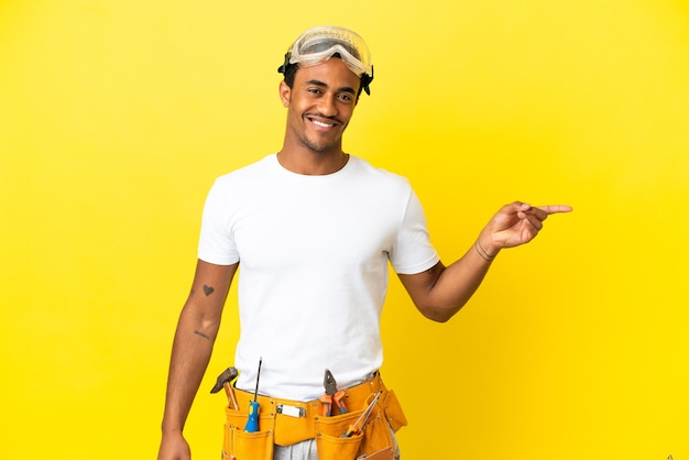 African american electrician man over isolated yellow wall pointing finger to the side