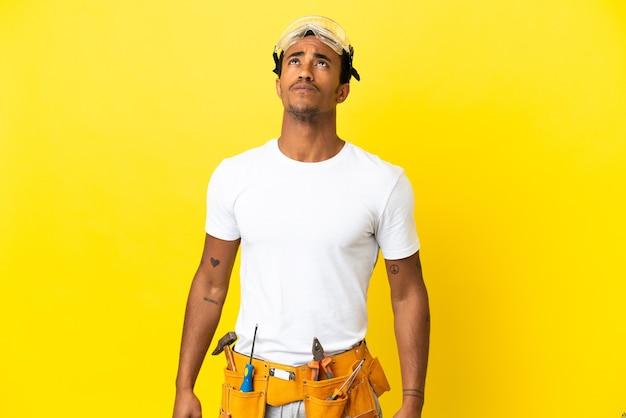 격리 된 노란색 벽에 아프리카 계 미국인 전기 남자를 찾고