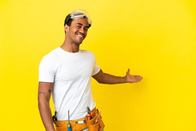 고립 된 노란색 벽에 아프리카 계 미국인 전기 남자와 서 초대를 위해 손을 옆으로 확장