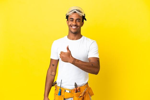 제스처를 엄지 손가락을 포기 고립 된 노란색 벽 위에 아프리카 계 미국인 전기 남자