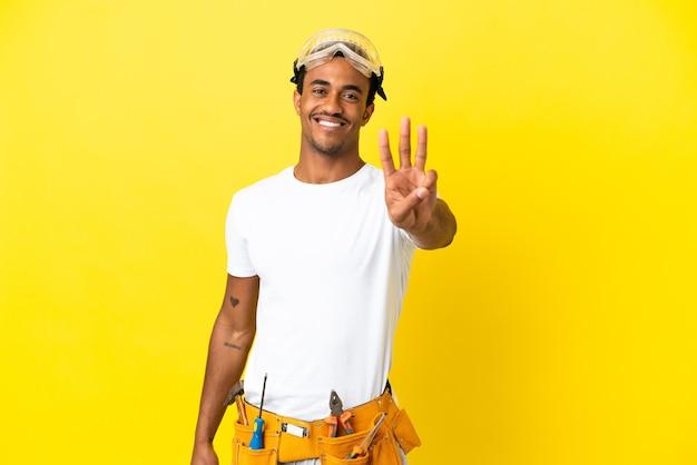 고립된 노란색 벽 위에 있는 아프리카계 미국인 전기 남자는 행복하고 손가락으로 세 개를 세고 있다