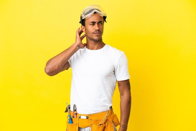 의심을 품고 고립된 노란 벽 위에 아프리카계 미국인 전기 남자