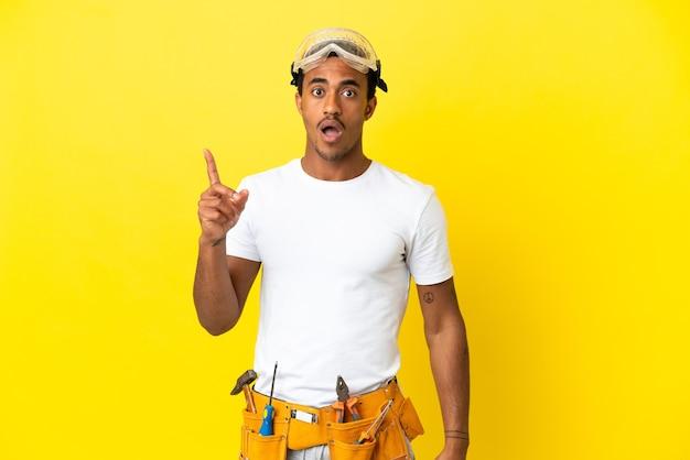손가락을 들어 올리는 동안 솔루션을 실현하려는 고립 된 노란색 벽 위에 아프리카 계 미국인 전기 남자