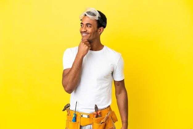 격리 된 노란색 벽에 아프리카 계 미국인 전기 남자 측면을 찾고 웃 고