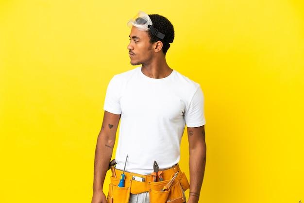측면을 찾고 고립 된 노란색 벽 위에 아프리카 계 미국인 전기 남자