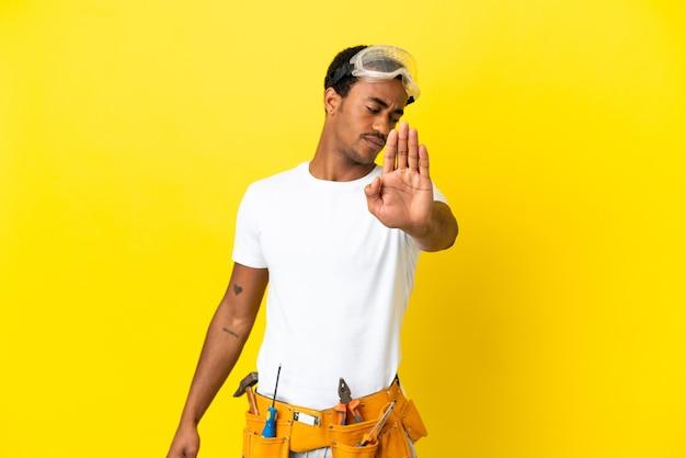 고립된 노란 벽 너머로 아프리카계 미국인 전기 기술자가 정지 제스처를 취하고 실망했다