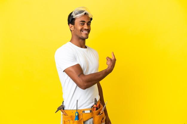 뒤로 가리키는 고립 된 노란색 벽 위에 아프리카 계 미국인 전기 남자