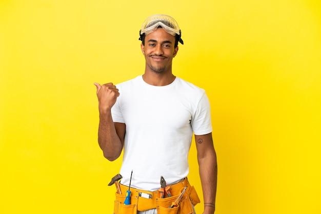 제품을 제시하기 위해 측면을 가리키는 격리 된 노란색 벽 위에 아프리카 계 미국인 전기 남자