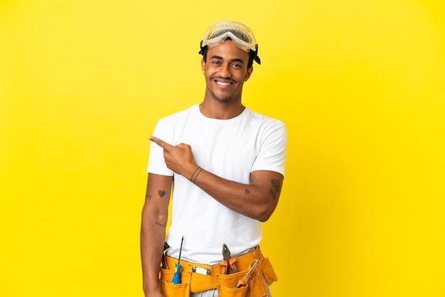 제품을 제시하기 위해 측면을 가리키는 고립된 노란색 벽 위에 아프리카계 미국인 전기 남자
