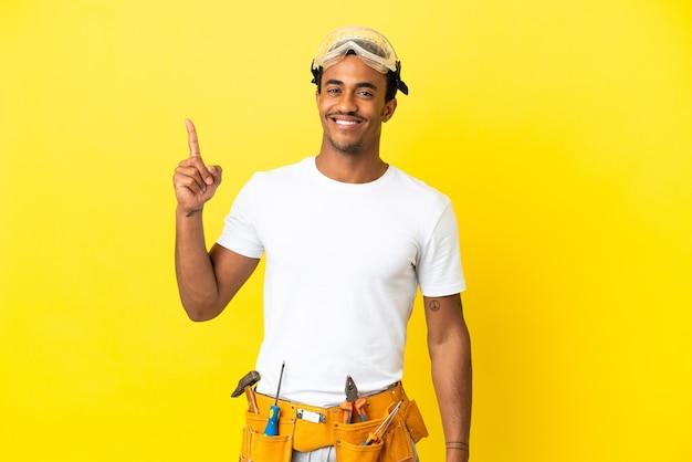 멋진 아이디어를 가리키는 고립된 노란색 벽 위에 아프리카계 미국인 전기 남자