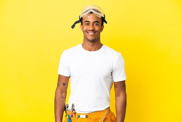 엉덩이에 팔을 포즈와 미소 격리 된 노란색 벽 위에 아프리카 계 미국인 전기 남자
