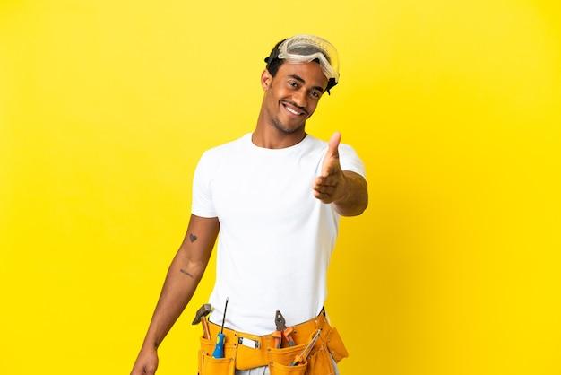 좋은 거래를 닫기 위해 악수 고립 된 노란색 벽 위에 아프리카 계 미국인 전기 남자