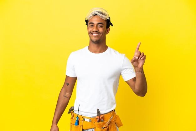 고립 된 노란색 벽을 통해 아프리카 계 미국인 전기 남자 보여주는 최고의 기호에 손가락을 들어 올려