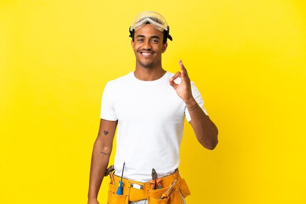손가락으로 확인 표시를 보여주는 고립 된 노란색 벽 위에 아프리카 계 미국인 전기 남자
