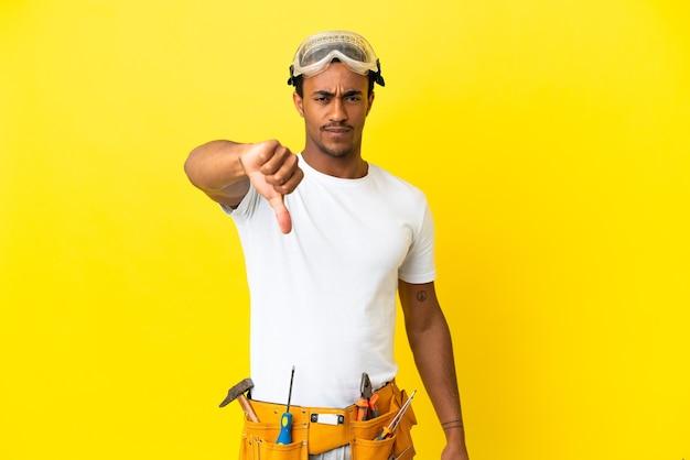 부정적인 표정으로 엄지손가락을 아래로 보여주는 고립된 노란색 벽 위에 아프리카계 미국인 전기 남자
