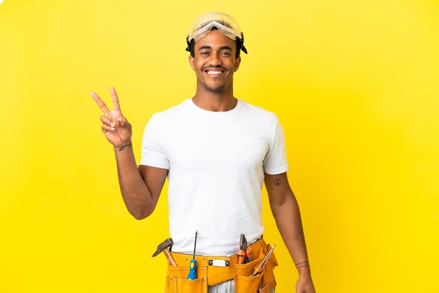 격리 된 노란색 벽 웃 고 승리 기호를 보여주는 아프리카 계 미국인 전기 남자