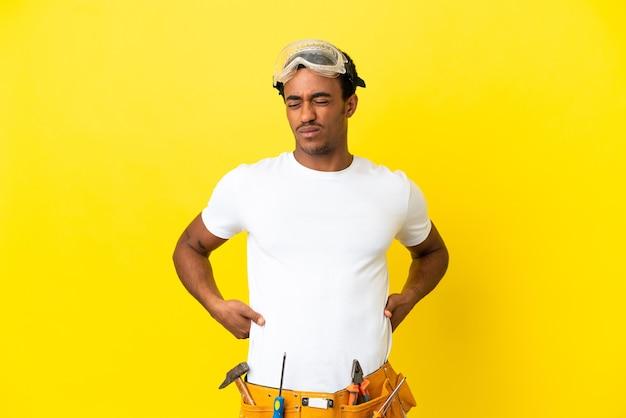 노력을 했다는 이유로 요통으로 고통받는 외딴 노란 벽 너머에 있는 아프리카계 미국인 전기 남자