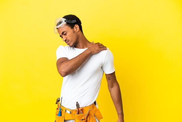 Афро-американский электрик над изолированной желтой стеной страдает от боли в плече за то, что приложил усилие