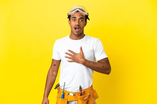 격리 된 노란색 벽 위에 아프리카 계 미국인 전기 남자는 놀라게 하 고 바로 보면서 충격