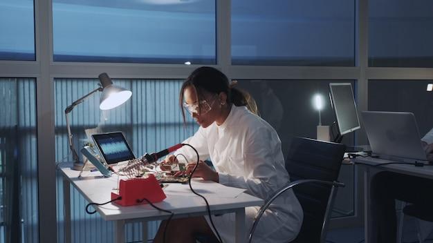 실험실에서 멀티 미터 테스터 및 기타 전자 장치를 사용하는 아프리카 계 미국인 전자 전문가