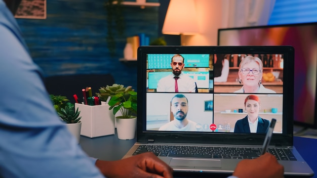 深夜に机に座っているラップトップを使用してオンラインでパートナーとリモートで話し合っているアフリカ系アメリカ人の従業員。仮想会議で話す最新技術ネットワークワイヤレスを使用するフリーランサー