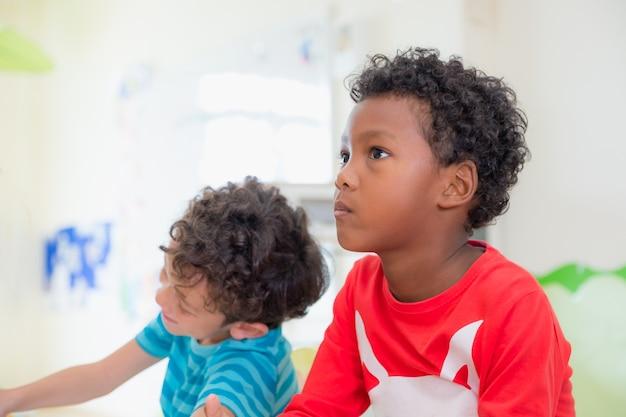 Афроамериканец этнического ребенка с капризной эмоции, сидя в классе в детском саду
