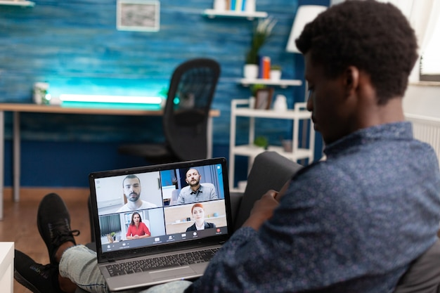 会議のウェブカメラ通信を使用してインターネット経由で共同接続するアフリカ系アメリカ人の民族男性...