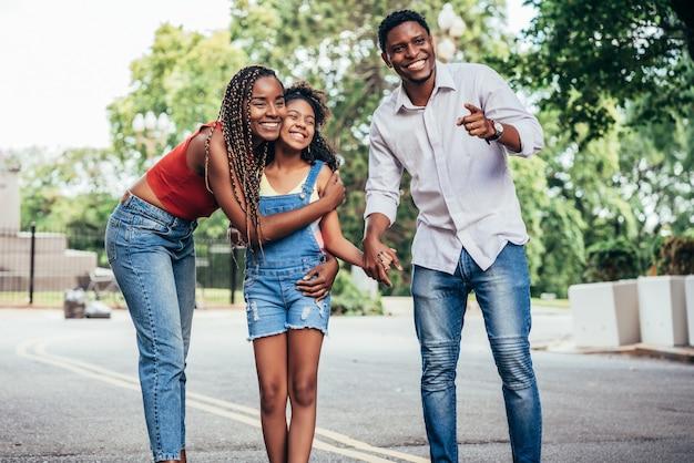 아프리카계 미국인 가족은 야외에서 거리를 걷는 동안 함께 하루를 즐기고 있습니다. 도시 개념입니다.