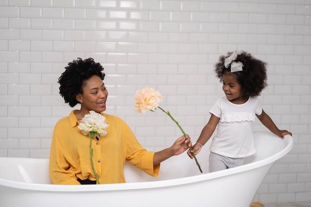 아프리카 계 미국인 가족, 행복 한 엄마와 아기 딸 재미와 화장실에서 함께 연주