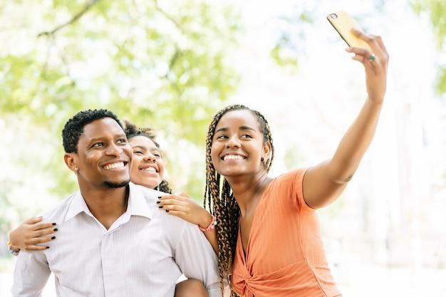 아프리카 계 미국인 가족 재미와 휴대 전화와 함께 셀카를 복용하는 동안 공원에서 하루를 즐기고 있습니다.