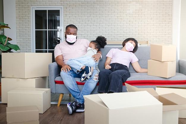 アフリカ系アメリカ人の家族が新しい家に引っ越し、居間のソファで休む