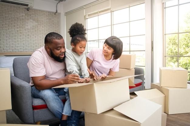 アフリカ系アメリカ人の家族が新しい家に引っ越す紙箱を開梱するのを手伝ってください