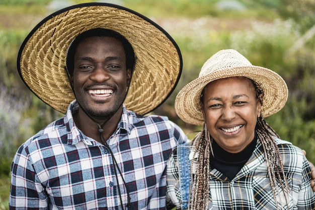 African american farmers smiling on camera during harvest period - focus on faces