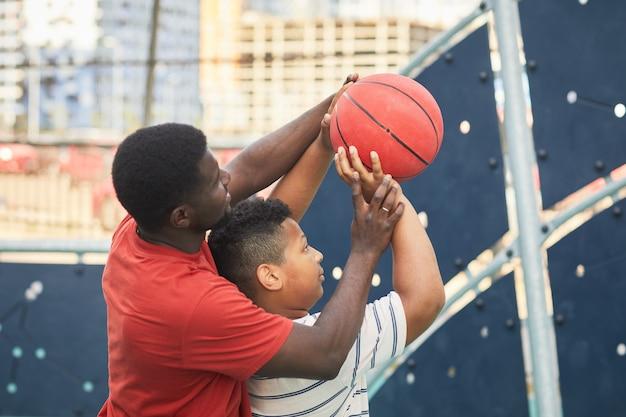 フープでバスケットボールを投げるように彼に教えている間息子の手の位置を調整するオレンジ色のtシャツのアフリカ系アメリカ人の父