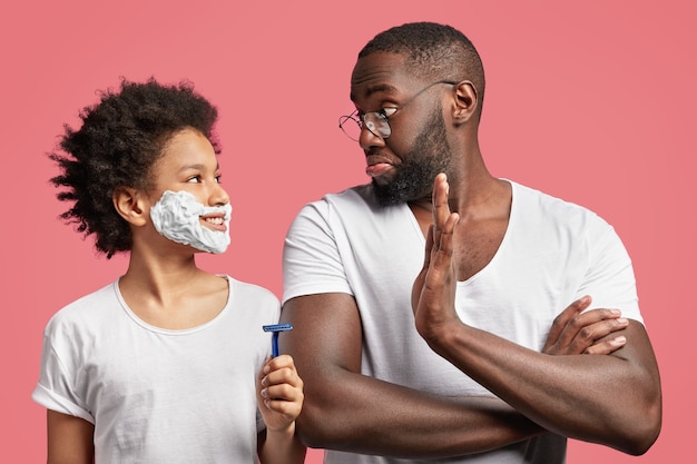 African-american father and son with shaving cream