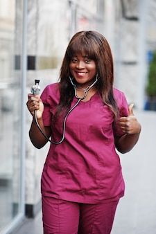African american female doctor at red lab uniform with stethoscope. medicine, profession and healthcare concept.