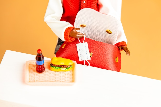 African-american female doll hand hold mask next to fastfood on a table