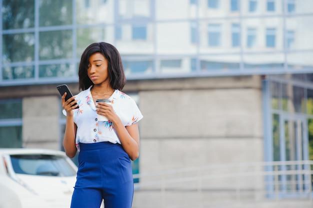 アフリカ系アメリカ人の女性起業家がオンラインバンキングを使用してスマートフォンから離れた場所に送金する