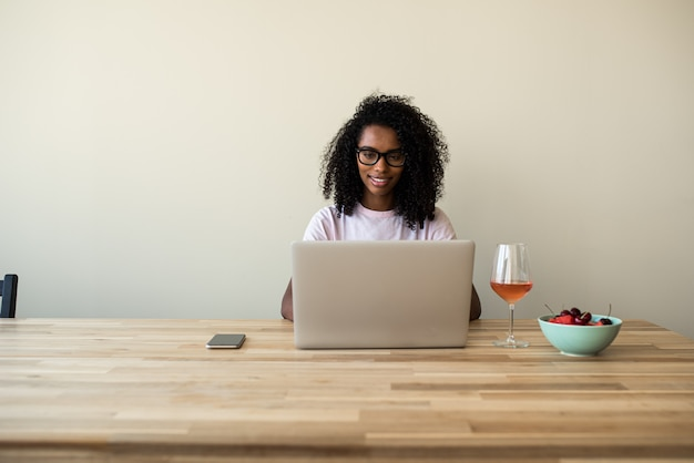 Афро-американский женский фрилансер с помощью ноутбука на дому