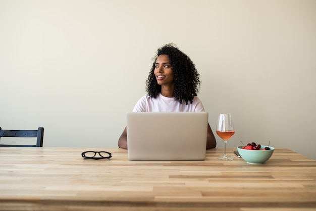African american female freelancer using laptop at home