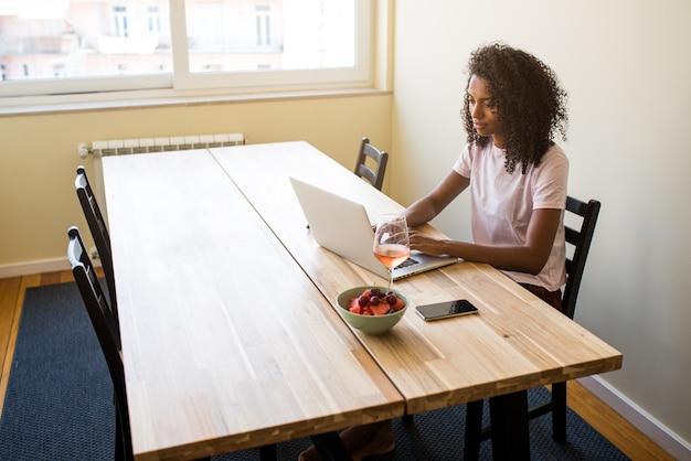 Афро-американский женский фрилансер с помощью ноутбука на кухне