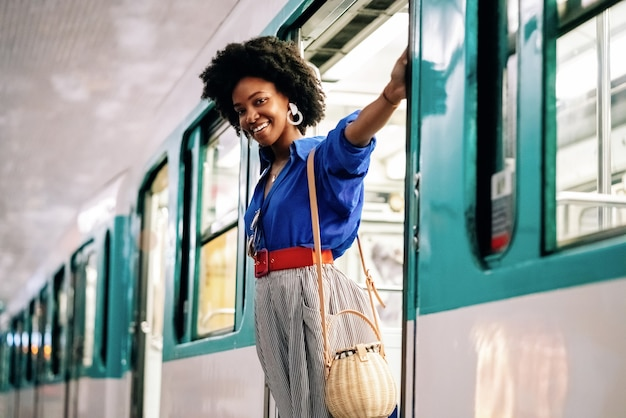 電車のドアにぶら下がっているアフリカ系アメリカ人の女性