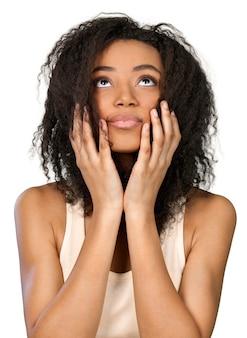 顔に手を上げて見上げるアフリカ系アメリカ人女性-孤立