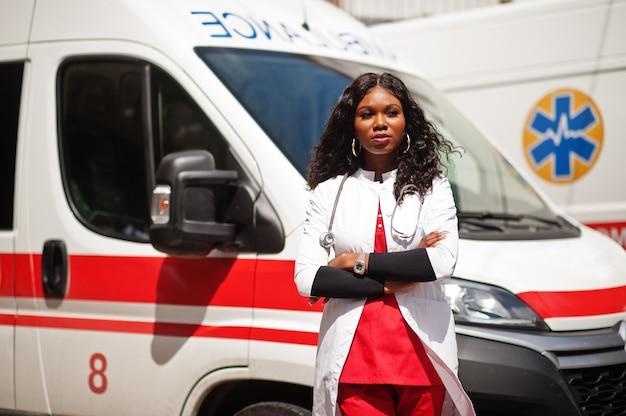 救急車の前に立っているアフリカ系アメリカ人の女性救急隊員